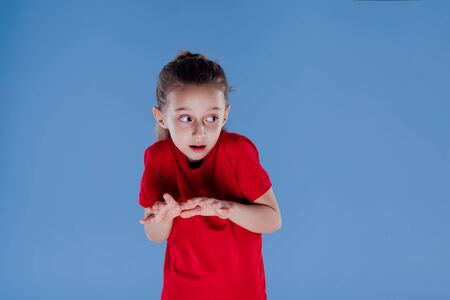 scared little girl looking away dressed in red T-shirt, isolated on blue background, in studio 版權商用圖片
