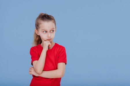 Serious thoughtful little girl in casual red wear looking away while standing against blue background