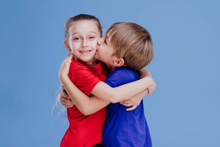 little boy kissing on the cheek on the little girl isolated on blue background, in studio