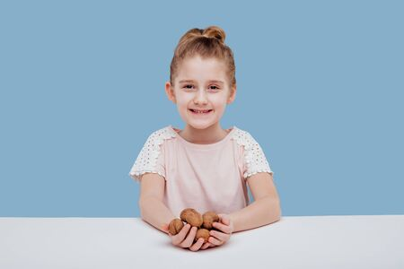 portret of little girl with walnuts in hand isolated on blue background, sitting at a table