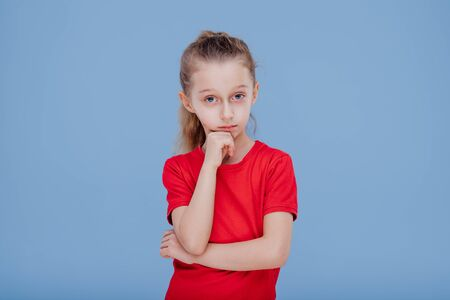 Thoughtful doubtful little girl in red t shirt touching chin and looking at camera, isolated on blue background