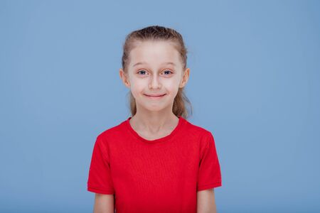 Funny surprised little girl in red t shirt staring at camera dressed in red T-shirt, isolated on blue background, in studio 版權商用圖片