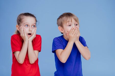 two scared children with hands on face isolated on blue background, in studio Stockfoto