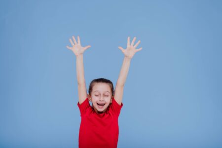 Cheerful active little girl in red outfit raising arms and jumping while having fun and celebrating success in studio with blue background