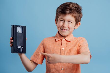 handsome child with video tape, isolated on blue background, poiting 版權商用圖片