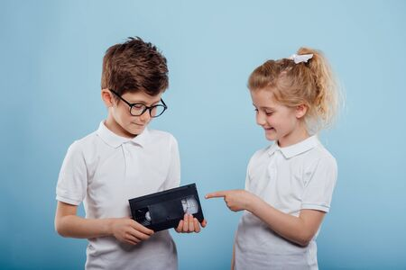 two smiling childs boy and girl with video tape, isolated on blue background, old gadgets