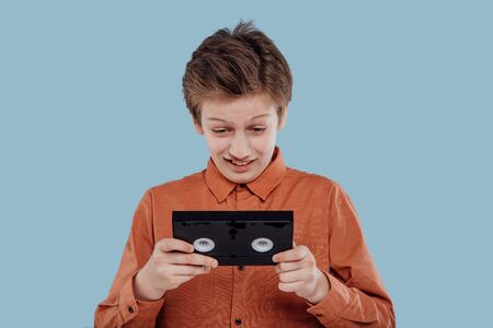 amazed preteen with video tape, isolated on blue background, old gadgets