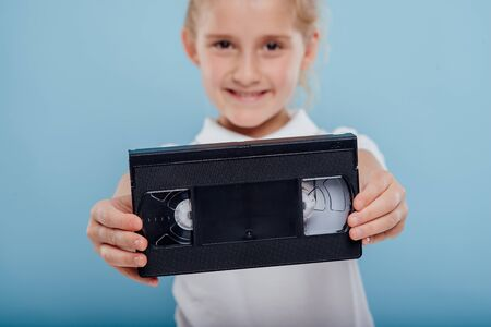close up, little girl with video tape, isolated on blue background, old gadgets