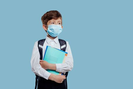 Little pensive male schoolchild in blue face mask in uniform with backpack standing on blue