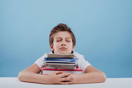 Tired young boy and books. Tired young boy sitting and sleeping with his head on the books, sitting at the table, isolated on blue background