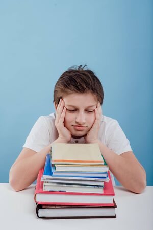 tired boy with books on the table, sitting at the table, isolated on blue background