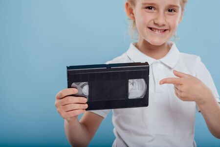 Little girl pointing to video tape, isolated on blue