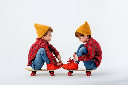two tired little boys are sitting on the skateboard, dressed in red shirt with squares and jeans, isolated on white background, studio shot Reklamní fotografie
