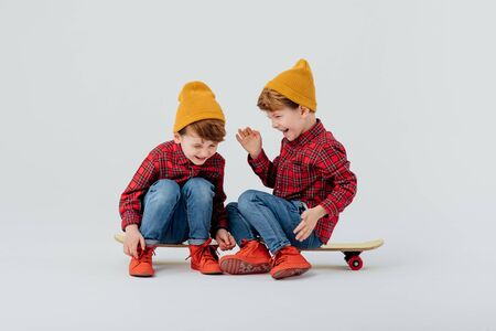 Positive twin boys in stylish outfit relaxing on skateboards on white background in studio and laughing at joke together