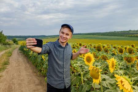 farmer in the sunflower field, recording content for the lifestyle blog vlog, modern farmer using social media for marketing