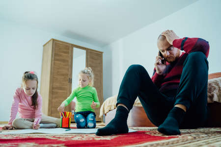 Stressed Man With his kids little girls From Home, talking on the phone, Tired young father overwhelmed with household chores
