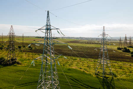 Drone flying over agricultural land and electric high voltage pylon against beautiful sky. Farmer fertile field. Agriculture and energy concept Stock Photo