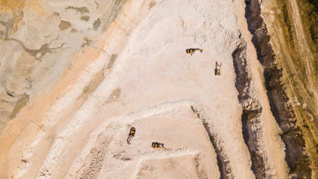 the flight of the drone over a quarry of sand and white stone, in the image you can see excavators that are stopped. aerial view of the stone and sand industry