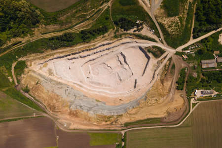 Aerial view industrial of opencast mining quarry with lots of machinery at work view from above. Extraction of white stone, sand