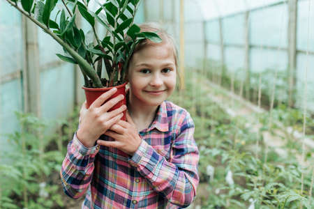 happy kid girl with flower in pot. greenhouse with houseplants. child looking at camera and holds a big potted flower in his hand Stock Photo