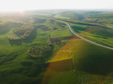 Aerial drone overhead of cars driving down straight road through leafless forest valley at sunset. Highway go through european ecosystem wildlife habitat natural environment concept Scandinavia 4K. Stock Photo