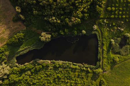 aerial view top view of a small lake among farmland. 4K drone shot