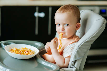 home in the kitchen little boy boy eating spaghetti pasta with red sauce. baby boy eating appetizing pasta alone Stock Photo