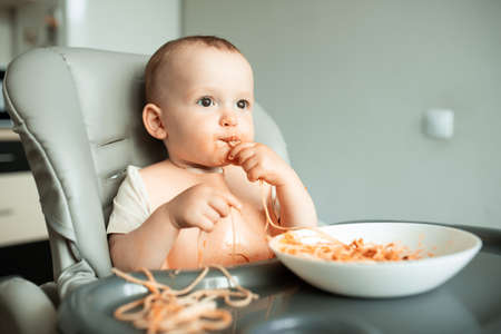 Healthy vegan breakfast, tasty pasta with red sauce is eaten by a very nice and cute baby boy. carefree childhood Stock Photo