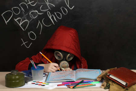 A child at a desk with a gas mask