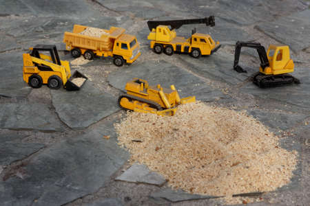 Toy models of construction equipment in transporting sawdust
