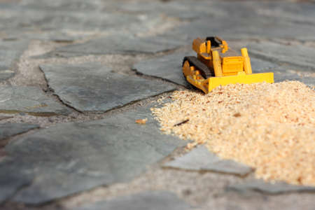 Toy bulldozer pushes a bunch of sawdust on the stones