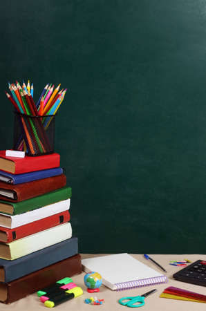 School theme with books on a green background Standard-Bild