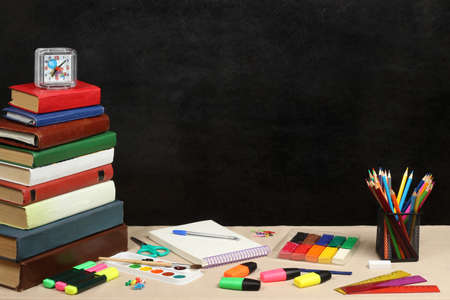 School theme with books with colors plasticine and watch black background Standard-Bild
