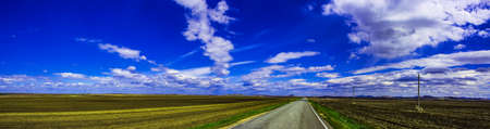 panoramic road in the field beautiful clouds