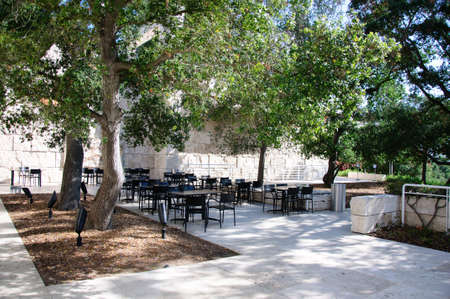 Landscaped Garden with Dining Tables Set in the Shade of Trees photo