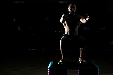 crouches: Young sportsman crouches before workout in gym