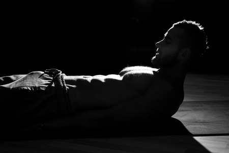 abdominal muscles: Handsome man exercising abdominal muscles at the gym