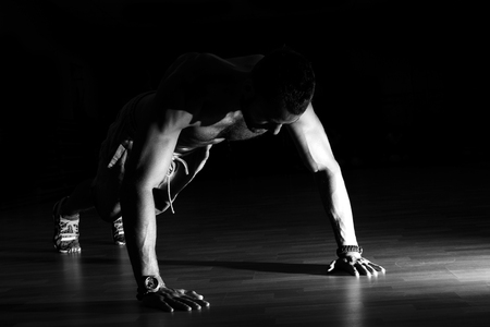 strength training: Man making burpees during strength training in gym. Stock Photo