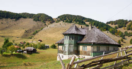 Old house located on the top of the Carpathian Mountains of Romania photo