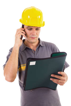 Young construction worker speaking on cellphone while reading a document photo