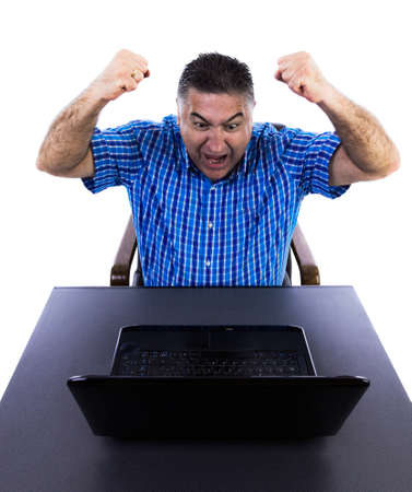 Happy businessman celebrating his glory days in his office looking at the accounts on his laptop Stock Photo