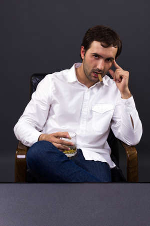 The portrait of man smoking a cigar accompanied by a glass of whiskey in his office