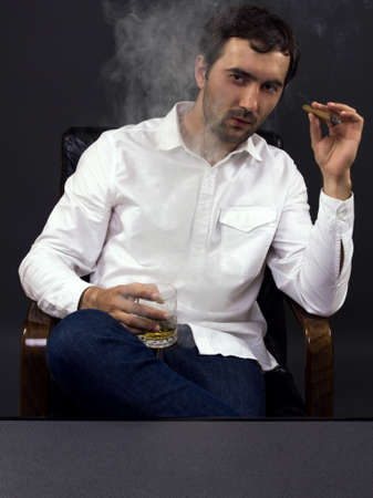 A man smoking a cigar while enjoying a glass of whiskey photo