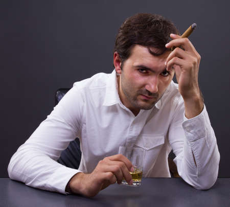 Disappointed man gets drunk on whiskey and a cigar thinking of a solution photo