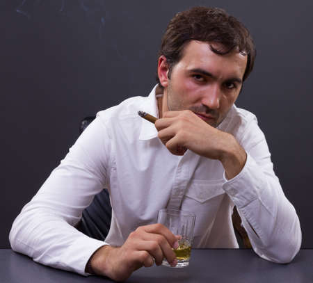 Young businessman drinking a glass of whiskey in his office photo