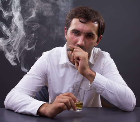 Young businessman smoking a cigar enjoying a glass of whiskey in his office, portrait of a young man photo