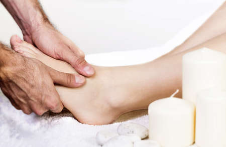 Physiotherapist giving a foot massage with his fingers photo