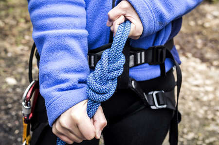 female hands holding a climbing rope with a secure node photo