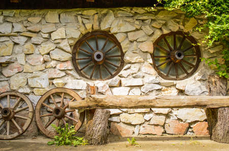 wooden bench in front of a farmhouse with stone wall and wheels wagon shaped windows photo