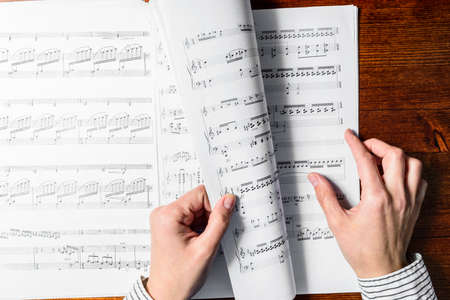 musical score: Female hands sight reading sheet music on wooden background